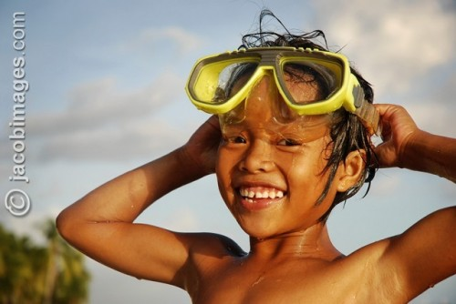 A local girl swimming with goggles smiles in the late evening sun