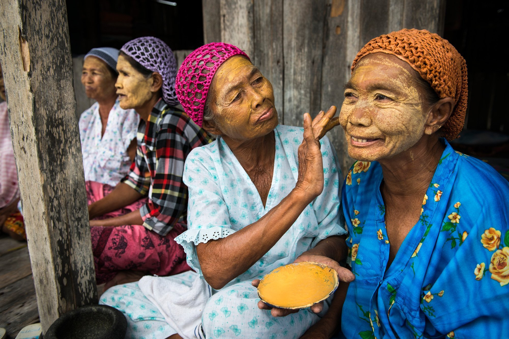 Sama-Bajau women applying a natural paste on their faces which they call burak. The paste is made from pounded rice, turmeric and some other ingredients to beautify their faces and act as a natural sunblock. (Tawi-Tawi, Philippines)